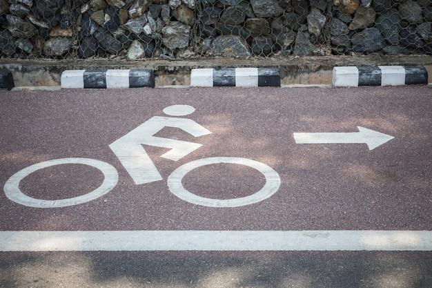 Ciérrese encima del signo o del icono blanco de la bicicleta en el camino Foto Premium