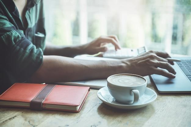 Ciérrese encima de la taza de café con el hombre de negocios que usa el ordenador portátil y la calculadora para calcular el presupuesto de auditoría o las finanzas de su compañía. Foto Premium