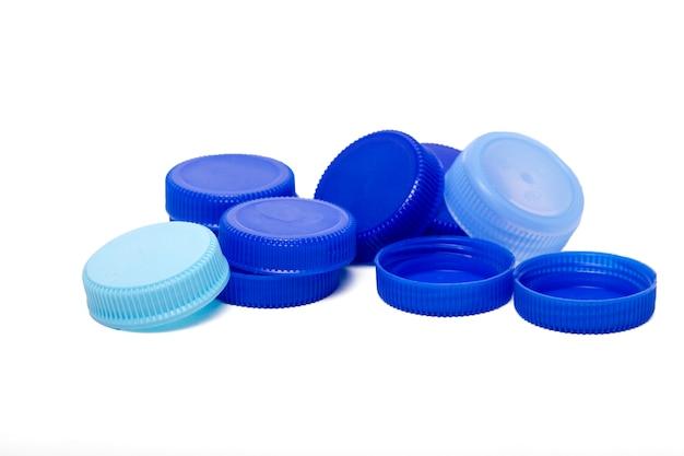 Ciérrese encima de vista de un manojo de casquillos plásticos azules de las botellas de agua aisladas en un fondo blanco. Foto Premium