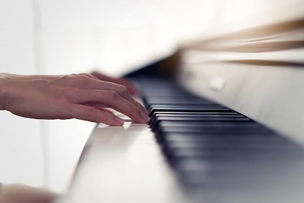 Ciérrese encima de la vista de las manos de la mujer que juegan el piano electrónico en casa. Foto Premium