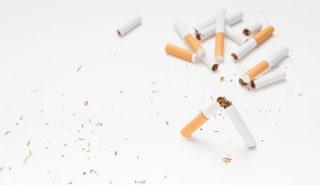 Cigarrillo roto y tabaco sobre superficie blanca. Foto gratis
