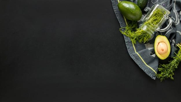 Cilantro y aguacate reducido a la mitad en tela de tableta contra fondo negro Foto gratis