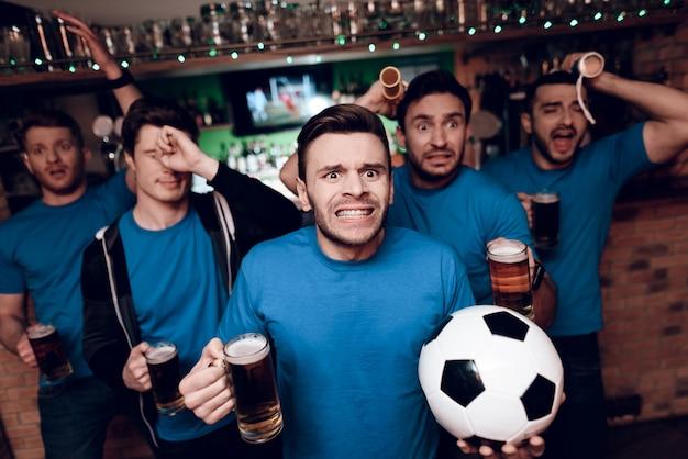 Cinco fanáticos del fútbol tristes porque su equipo pierde en el bar Foto Premium