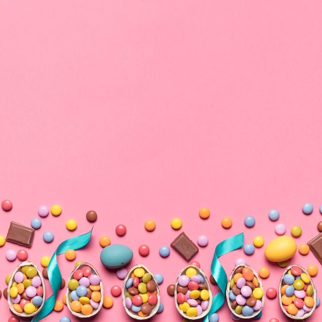 Cinta; caramelos de gemas y huevos de pascua con espacio para escribir el texto sobre fondo rosa Foto gratis