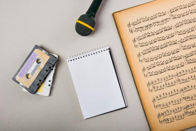 Cinta de casete; bloc de notas en espiral y micrófono con una vieja libreta musical vintage. Foto gratis