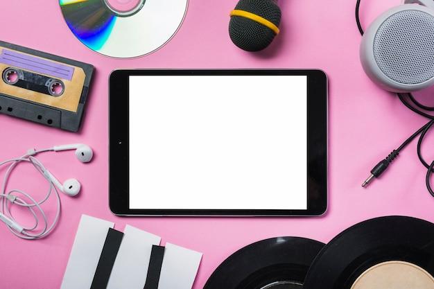 Cinta de casete; discos compactos; auricular; disco de vinilo; micrófono; altavoz; teclas de piano de papel alrededor de la tableta digital sobre fondo rosa Foto gratis