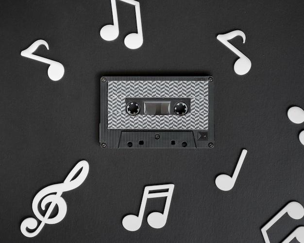 Cinta de cassette oscura con notas musicales blancas que la rodean Foto gratis
