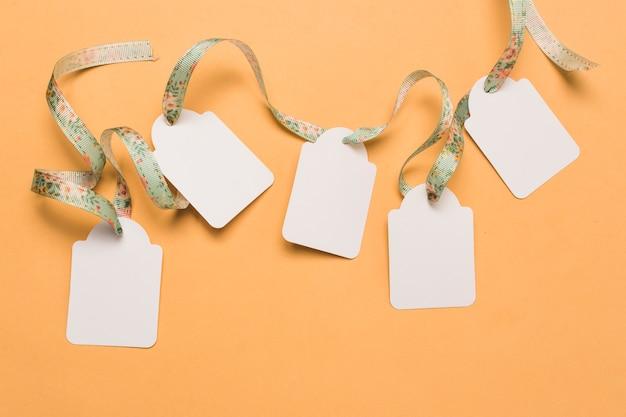 Cinta de diseño a través de etiquetas vacías dispuestas sobre una superficie amarilla brillante. Foto gratis