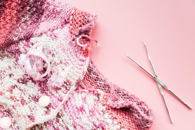 Cinta métrica con ganchillo y agujas sobre fondo rosa Foto gratis