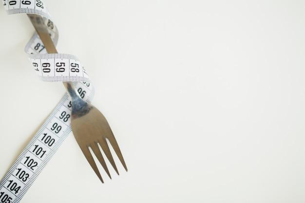 Cinta métrica y un tenedor en blanco Foto Premium