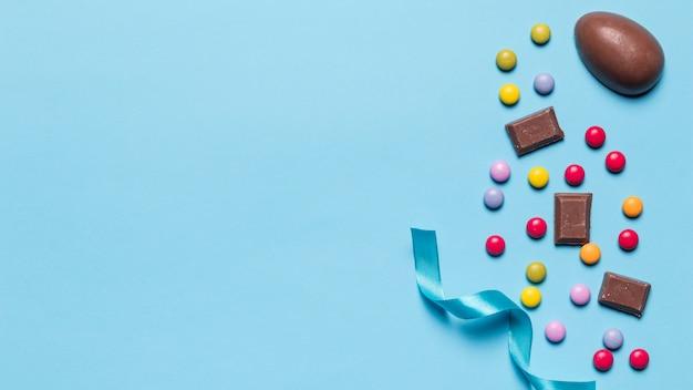Cinta de raso; caramelos de gemas y huevos de pascua con espacio para escribir el texto sobre fondo azul Foto gratis
