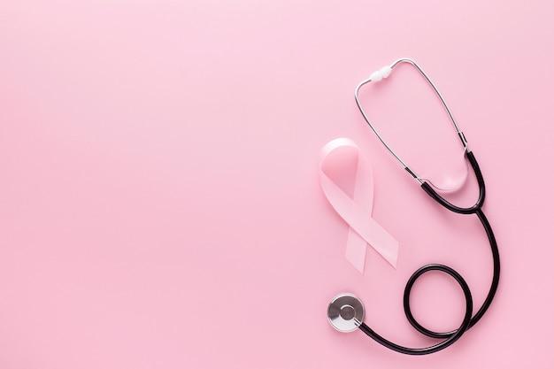 Cinta rosa y un estetoscopio sobre una superficie rosa Foto Premium