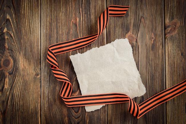 Cinta de san jorge y tarjeta de felicitación de papel sobre fondo de madera. día de la victoria o día del defensor de la patria. Foto Premium