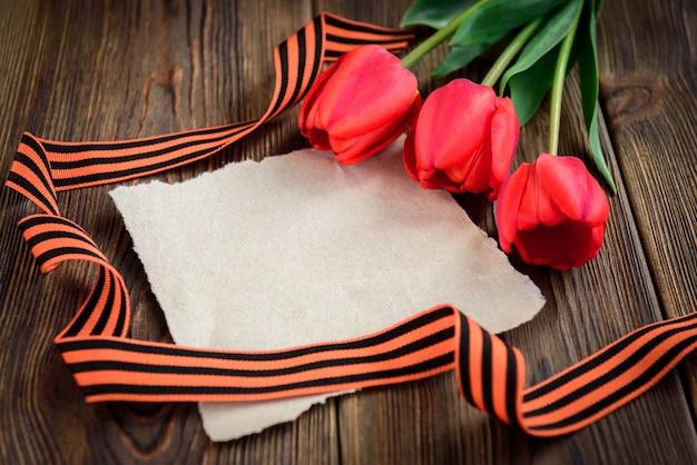 Cinta de san jorge, tulipanes rojos y tarjeta de felicitación de papel sobre fondo de madera. día de la victoria o día del defensor de la patria. Foto Premium