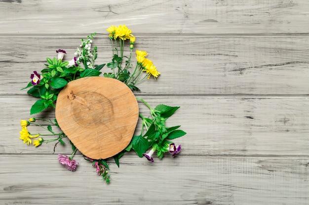 Círculo de madera con flores brillantes alrededor. Foto gratis