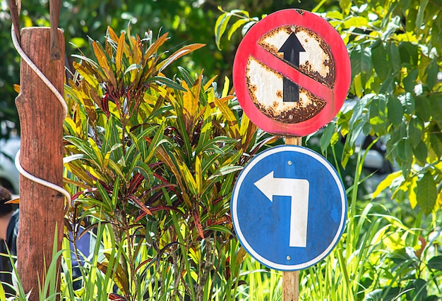 Círculo de señales de tráfico que está prohibido ir recto y girar a la izquierda fondo árbol borroso. Foto Premium
