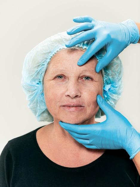 Cirujano haciendo un control de la piel de una mujer de mediana edad antes de la cirugía plástica Foto gratis