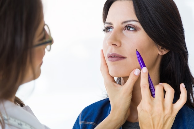 Cirujano plástico dibujando líneas punteadas en la cara de su paciente. Foto gratis