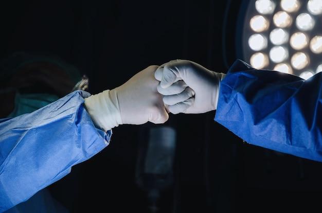 Cirujano unir manos juntas en la sala de operaciones en el hospital Foto Premium