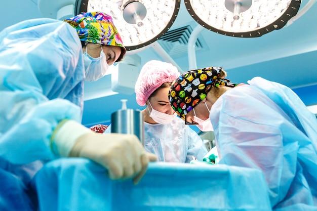 Cirujanos que operan a un paciente en quirófano Foto Premium