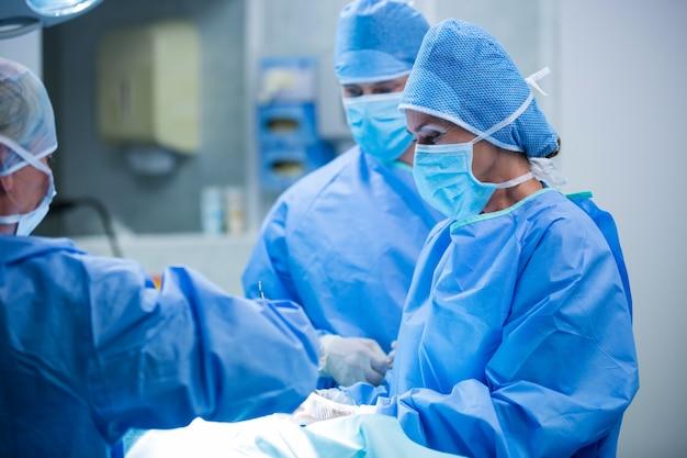 Los cirujanos que realizan la operación en la sala de operación Foto gratis