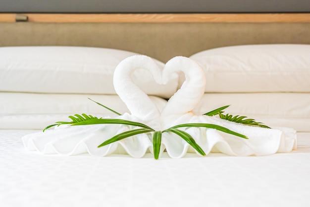 Cisne de toalla blanca en la decoración de la cama interior del dormitorio Foto gratis