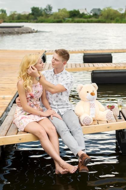 Cita romántica sorpresa. un chico joven y una chica en un muelle de madera. abraza y besa mientras estás sentado en el muelle. historia de amor romantica Foto Premium