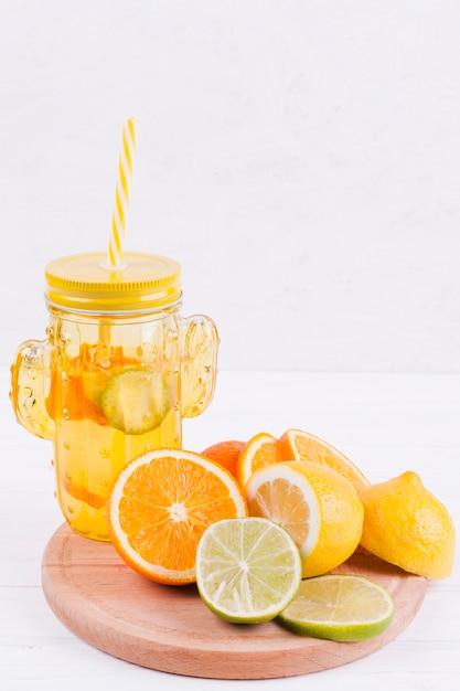 Cítricos y jugo sobre tabla de madera. Foto gratis