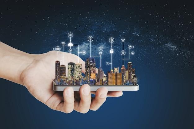 Ciudad inteligente, tecnología de la construcción y tecnología de aplicaciones móviles. mano que sostiene el teléfono inteligente móvil con tecnología de interfaz de programación de aplicaciones y holograma de edificios Foto Premium