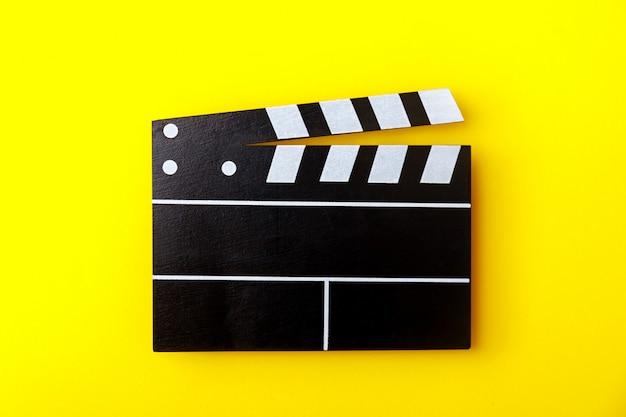 Claqueta de cine negro sobre fondo amarillo. la cinematografía moderna, el cine. Foto Premium