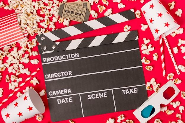 Claqueta rodeada de palomitas de maíz; entradas de cine; vidrio para llevar; pajitas y gafas de sol sobre fondo rojo Foto gratis