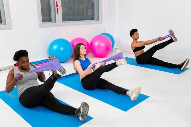 Clase de fitness haciendo ejercicios en colchoneta Foto gratis