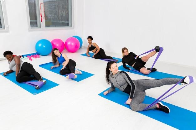 Clase de fitness con mujeres haciendo ejercicio Foto gratis