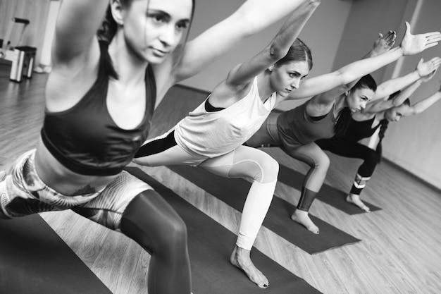 Clases grupales de yoga dentro del gimnasio. Foto gratis