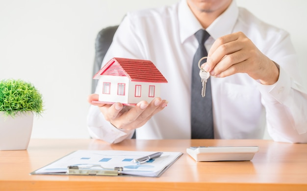 Clave de la casa en la protección de manos del agente de corredores de seguros del hogar Foto gratis