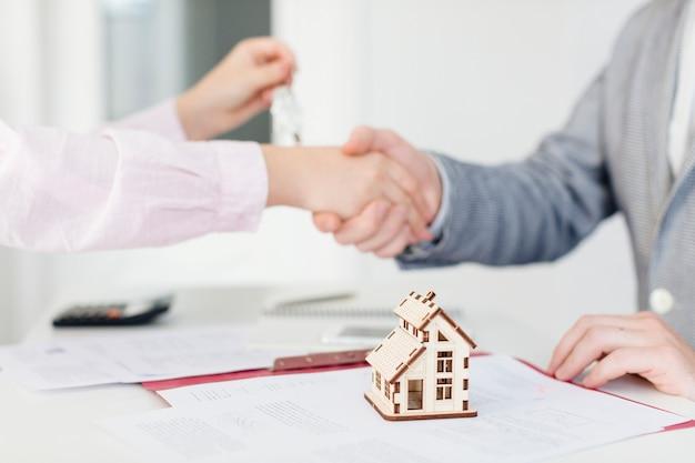 Cliente y agente de bienes raíces haciendo trato Foto gratis