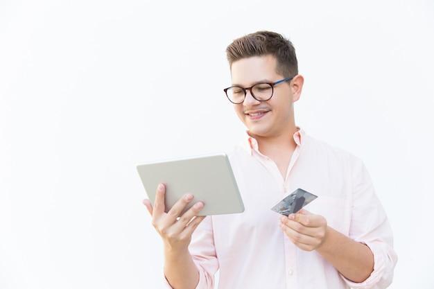 Cliente alegre con tableta y tarjeta de crédito pagando en línea Foto gratis