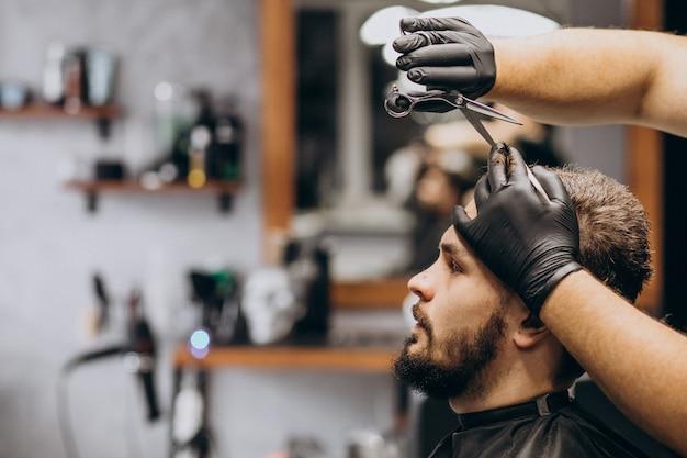 Cliente haciendo corte de pelo en un salón de peluquería Foto gratis