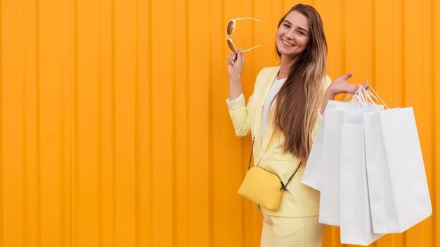 Cliente joven vistiendo ropa amarilla sobre fondo naranja Foto gratis