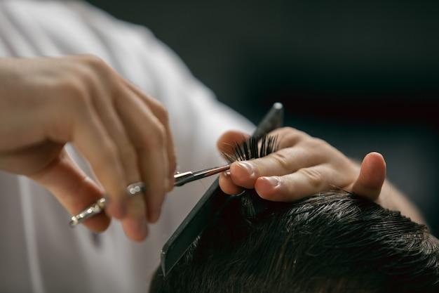 Cliente del maestro barbero, estilista durante la atención y un nuevo aspecto de peinado Foto gratis