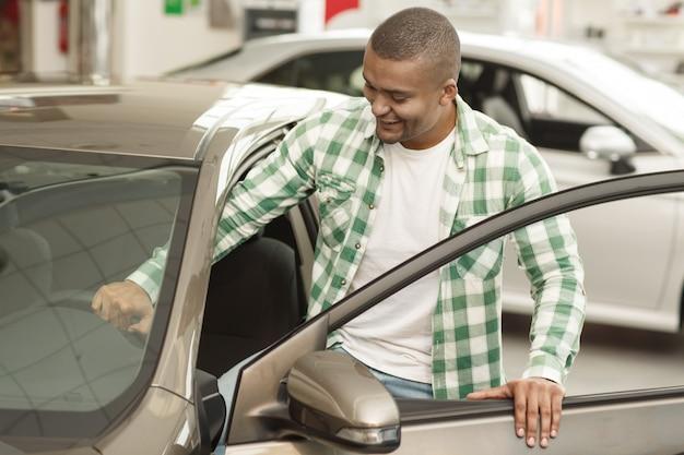 Cliente masculino atractivo subirse a un automóvil nuevo, elegir automóvil para comprar. Foto Premium
