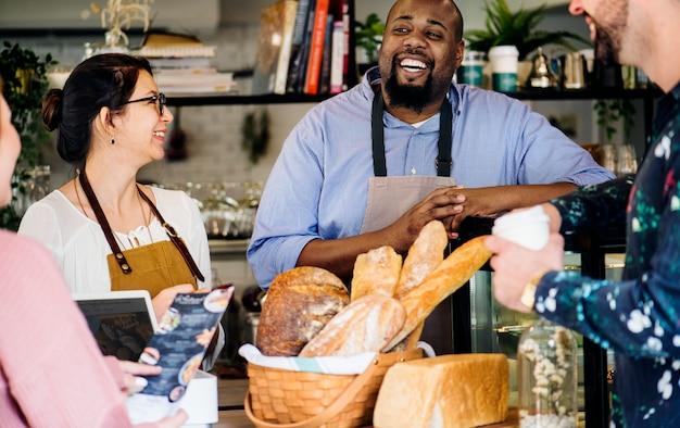 Cliente pidiendo pastelería en mostrador Foto Premium