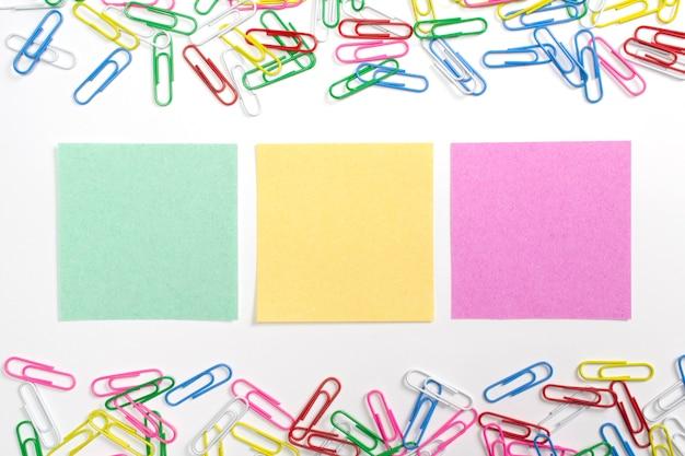 Clips de papel coloridos y 3 papeles de nota en el centro aislados en blanco. Foto gratis
