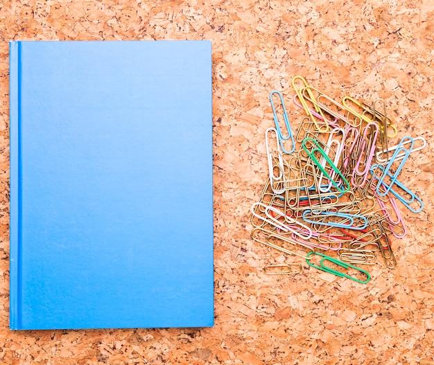 Clips de papel y cuaderno azul en tablero de corcho Foto gratis