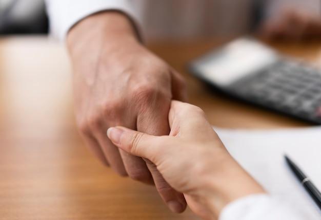 Close-up adultos dándose la mano en la oficina Foto gratis