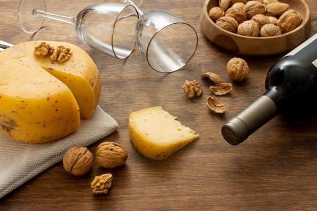 Close-up botella de vino y queso. Foto gratis