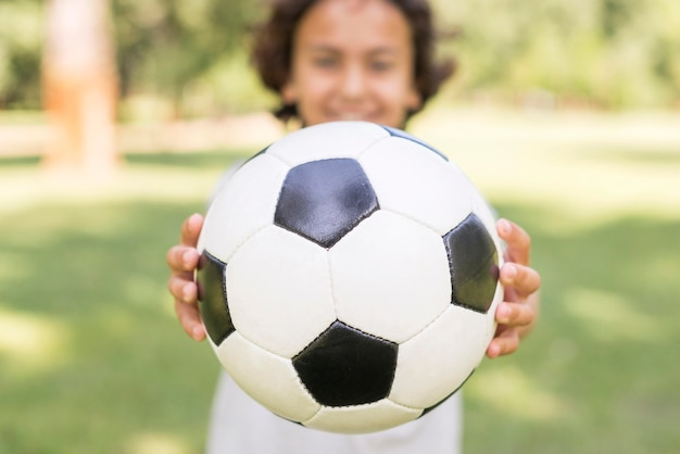 Close-up boy jugando con pelota de futbol Foto gratis
