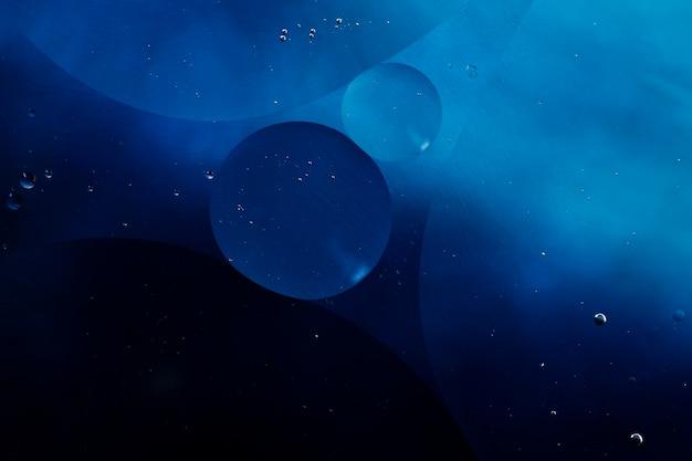 Close-up burbujas y gotas aceitosas en colorido telón de fondo acuoso Foto gratis