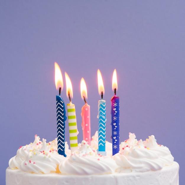 Close-up coloridas velas en delicioso pastel Foto gratis
