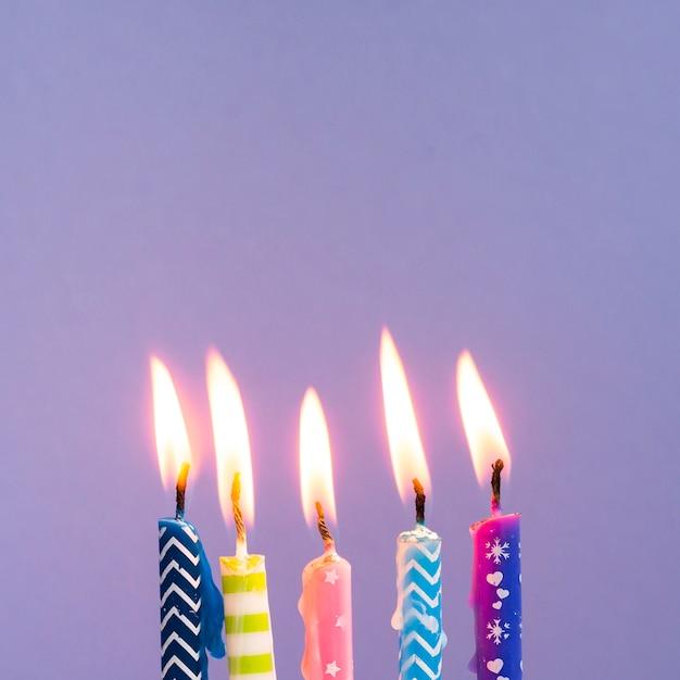Close-up coloridas velas sobre fondo morado Foto gratis